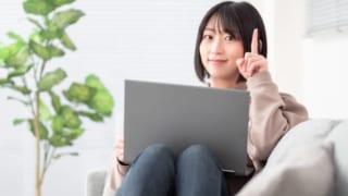 ソファーでPCを膝に置き、指を立てている女性の写真